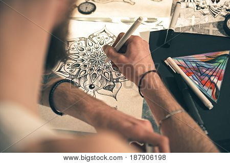 Man making calligraphic ornaments at table in salon. He turning back to camera. Picture concept