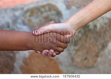 Two children´s hands of different races together shaking