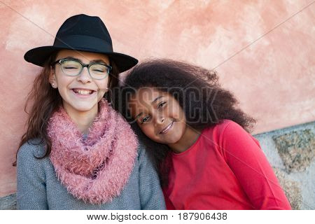 Two happy girls friends with stylish hats lauging