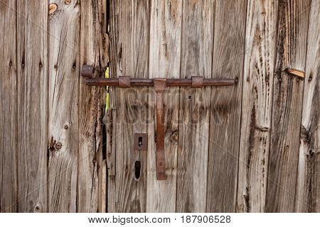 Closed rusty latch on an old wooden door
