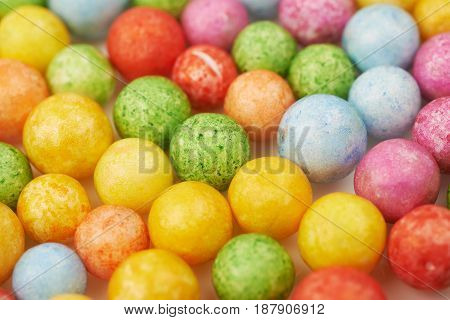 Surface coated with colorful balls or sphere shaped breakfast cereals as an abstract backdrop composition