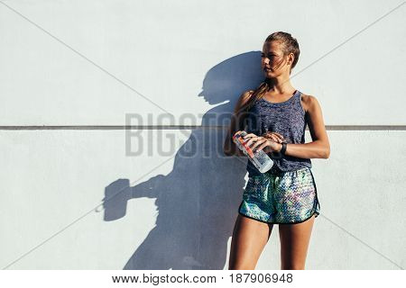 Portrait of young fitness woman standing outdoors with water bottle looking away against wall. Female runner resting after workout.