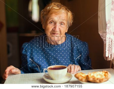 Elderly woman drinking tea. Russian or Ukrainian.