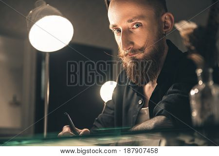 Low angle serene bearded male writing at table in room. He looking at camera
