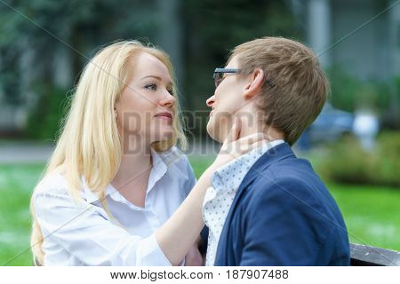 one blond european woman holding neck of her lover and waiting his kissing at warm summer day