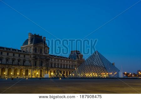 PARIS, FRANCE - DECEMBER 9, 2016: View of famous Louvre Museum with Louvre Pyramid at evening. Louvre Museum is one of the largest and most visited museums worldwide.
