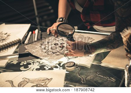 Focus on tattoo hand of female viewing picture under magnifier while sitting at table. Close up