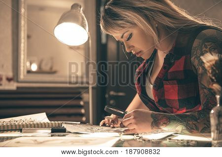 Focus on low angle side view serene woman looking at tattoo image with lens