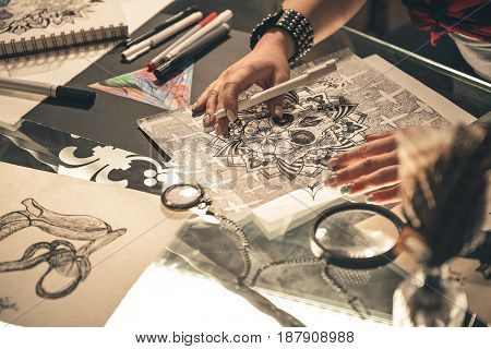 Focus on close up tattoo picture situating on desk near various art tools. Female hand drawing it