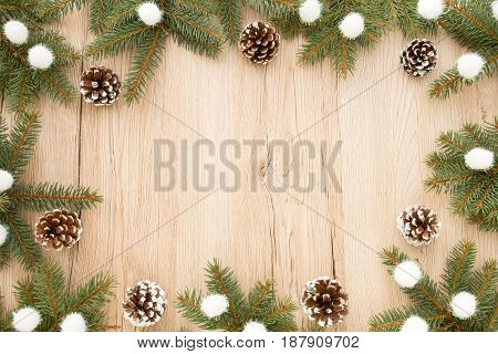 Christmas frame out of fir tree twigs snowy pine cones and white christmas glitter balls on brown wooden background with lots of copy space.
