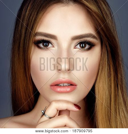 Fashion portrait of young beautiful woman with jewelry. Brown hair girl. Perfect makeup. Beauty style girl with ring