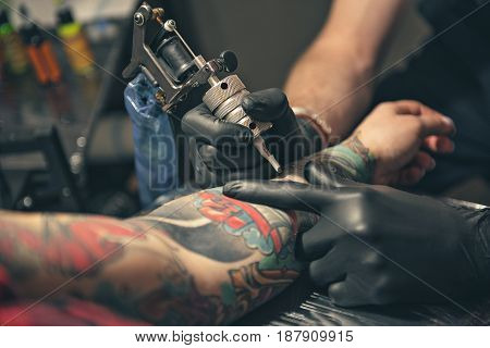 close up equipment for making tattoo art. Man doing picture on hand of woman