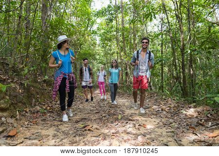 People Group With Backpacks Trekking On Forest Path, Young Men And Woman On Hike Mix Race Tourists Hiking