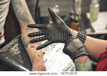 Close up female hand with rubber mitten. She preparing for drawing picture on body of man