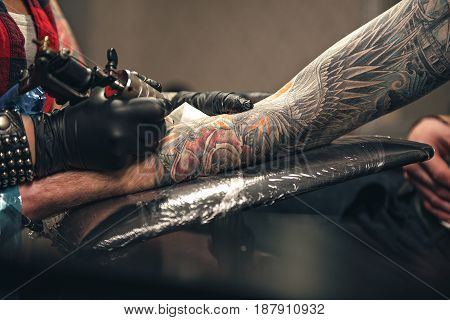 Close up arm leaning on soft surface. Master drawing tattoo on it with special instrument in salon