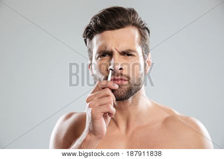 Confused bearded man trying to tweezers hair in nose isolated