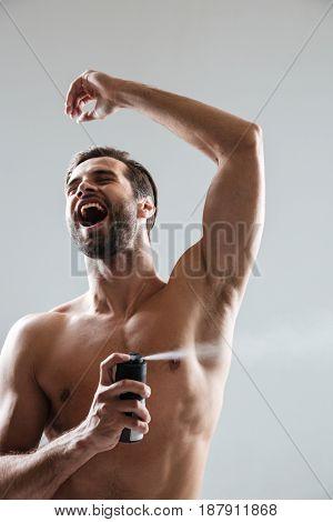 Happy man using deodorant with pleasure isolated