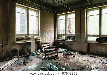 Room in daylight with big windows and furniture in old ruined abandoned industrial building or factory
