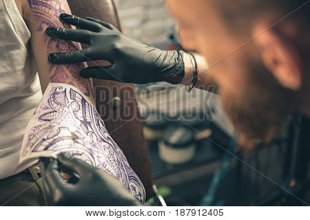 Man comparing tattoo image on hand of client with original in salon