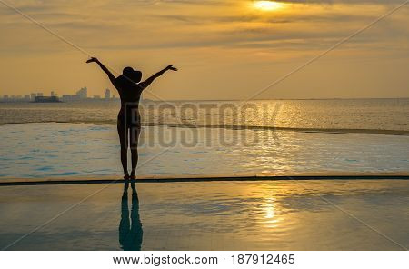 Woman holding hat relaxing at the pool on the sunset and twilight