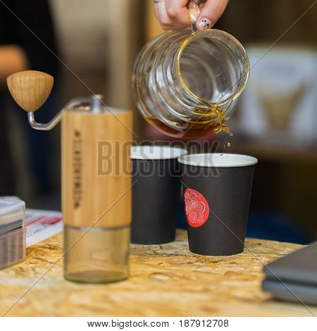 Hand of a barista girl pouring filtered coffee into paper cup with abstract logo.Close-up of drops of pouring coffee. Coffee culture and its varieties, service and catering concepts