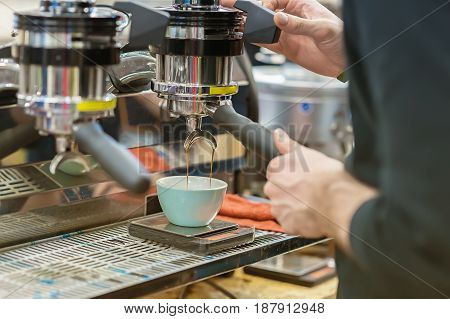 Barista, working at the bar. Making coffee in the coffee machine. Fresh espresso.. Coffee culture and professional coffee making, service, catering concepts