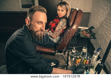 Portrait of cheerful male master putting color in technical device before making picture on hand of female client