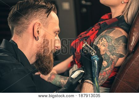 Side view of smiling bearded man doing tattoo on arm of young woman. She leaning at table