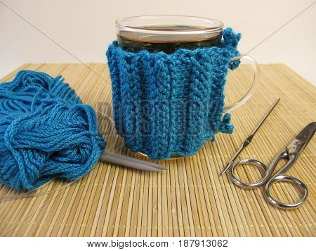 Knitted blue cup cozy for tea glasses