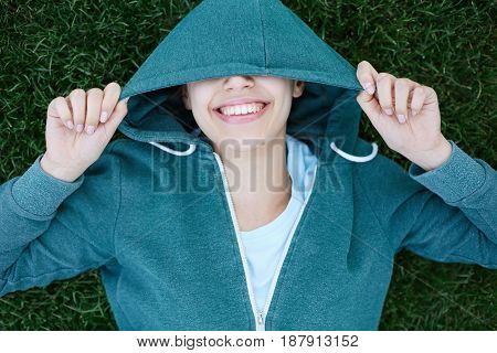 Portrait of young and sporty woman in sportswear lying on the green grass outside at the park on green meadow on cloudy day, Dnipro, Ukraine. The woman playfully puts the hood on her head, smiles, laughs and looks at the camera