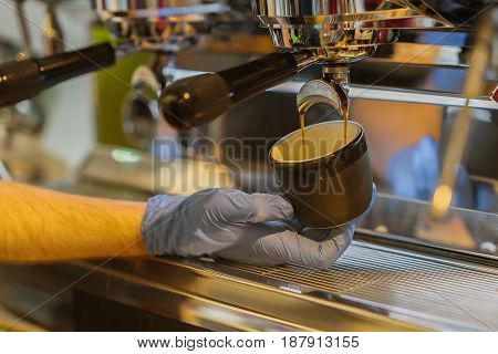 Close-up fresh espresso pours into the porcelain cup in the hand of a professional barista. Coffee culture and professional coffee making, service and catering concepts