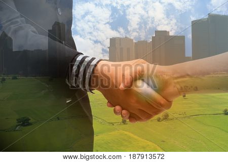 Double exposure of handshake with blur city and agriculture concept with the fake flarethe partnership between business man and farmer