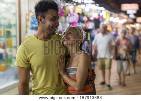 Couple Embracing On Street Market, Mix Race Man And Woman Happy Smiling Looking At Each Other Shopping