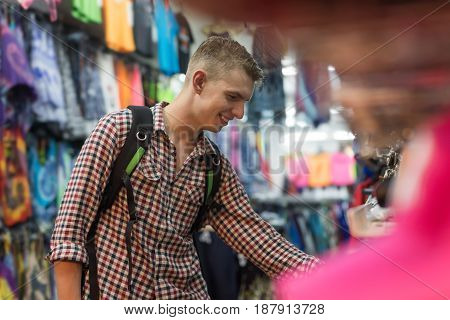 Young Man On Shopping Choosing Clothes, Guy Buyer Happy Smiling In Retail Store Selecting Clothes