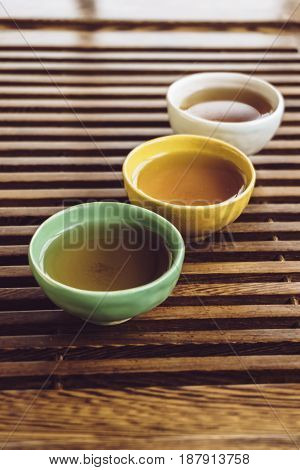 Tea cups on wooden tea table or tea board. Cups or pialas for Traditional Chinese tea Ceremony, vertical image