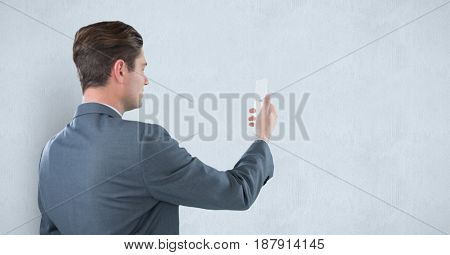 Digital composite of Rear view of businessman holding mobile phone