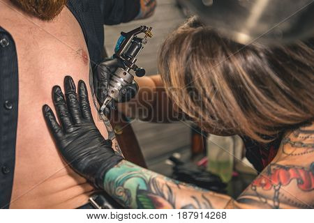 Female master doing tattoo on belly of man. He leaning on chair in apartment