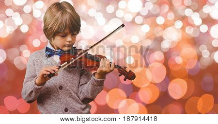 Digital composite of Little boy playing violin over bokeh