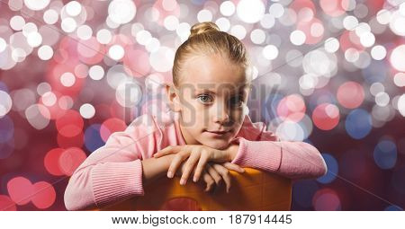 Digital composite of Portrait of girl sitting over bokeh