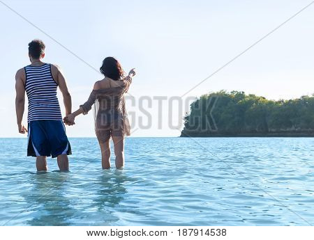 Couple Beach Summer Vacation, Man Woman In Water Point Finger To Copy Space Beautiful Young Guy Girl Back Rear View Sea Ocean Holiday Travel