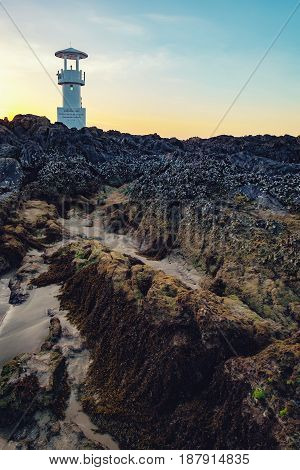 Lighthouse in the evening twilight Nang Thong Beach, Khao Lak, Thailand. Stones covered with seaweed in the foreground