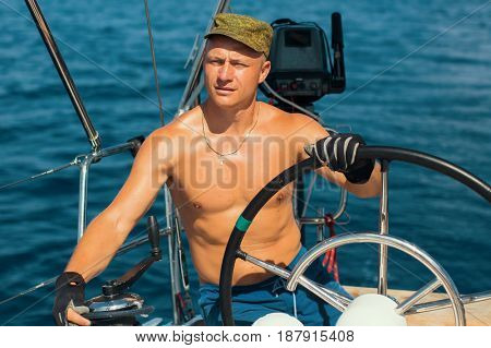Young man with naked body steers the sailing boat. Luxury yacht and cruise holiday.