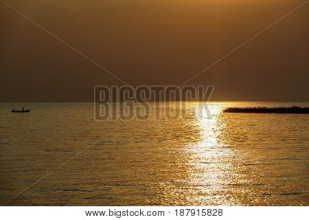 Long shot of boat arriving to coast at sunset