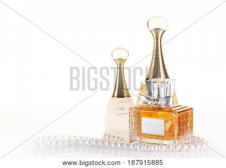 St.Petersburg, Russia - May 2017 - Christian Dior bottles of perfume and pearls on a white background with reflection. Illustrative editorial.