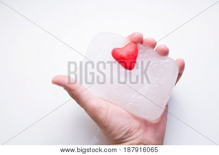 Masculine hand holds a heart of ice on a white background