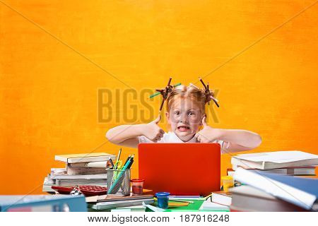 The Redhead teen girl with lot of books sitting with laptop at table on orange studio background. The education and back to school concept