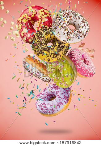Tasty donuts in motion falling on pastel red background, close-up.