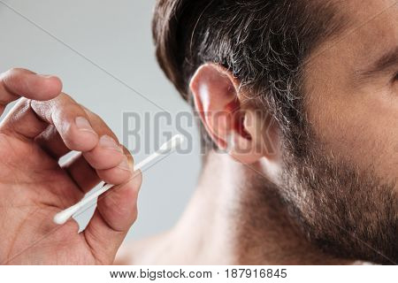 Close up shot of bearded man cleaning his ears isolated