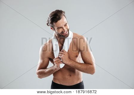 Young bearded man using towel and laughing isolated