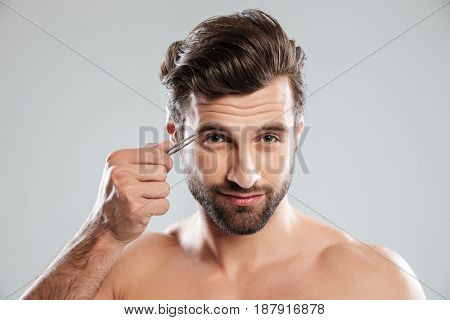 Bearded young man tweezering his eyebrows isolated over grey background